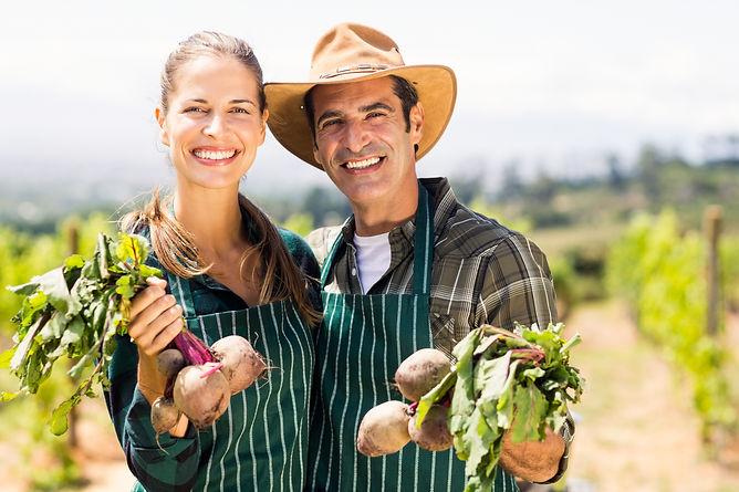 portrait-happy-farmer-couple-holding-lea