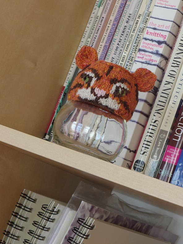 A glass jar with a knitted tiger collar