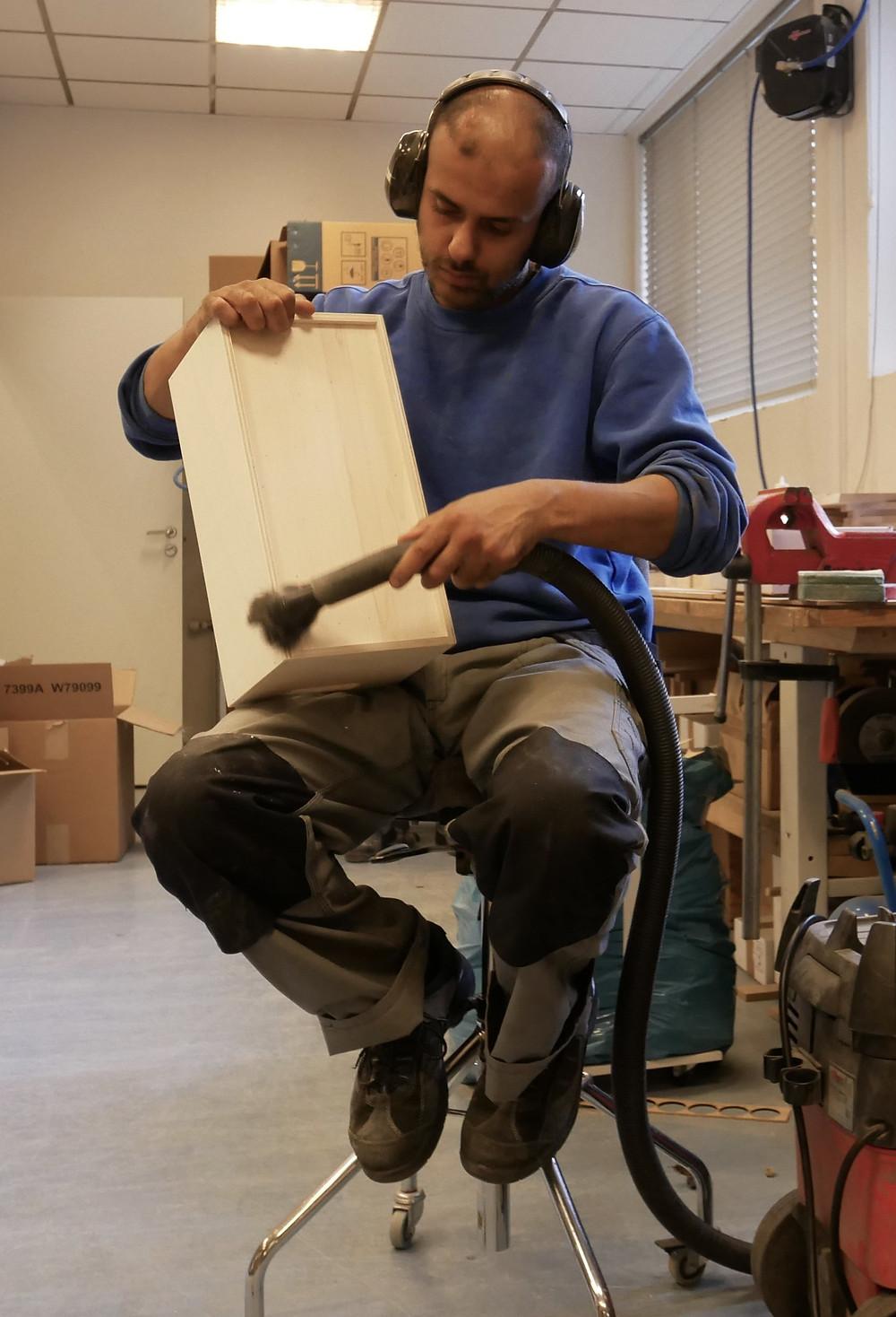 Ehtesham legger siste hånd på verket med bokkassene til Aschehoug. Før etikettene kan klistres på må kassene være helt støvfrie