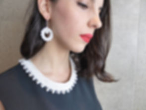 Woman wearing an Urbanknits silk and pearl handknit collar and matching earrings.
