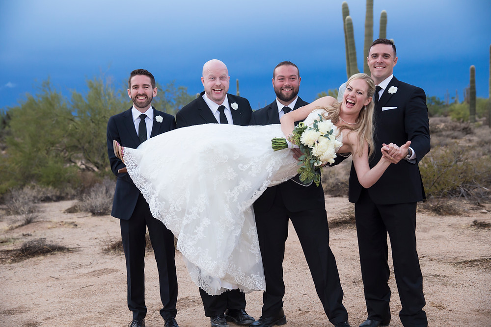 groomsmen lift the bride and laugh