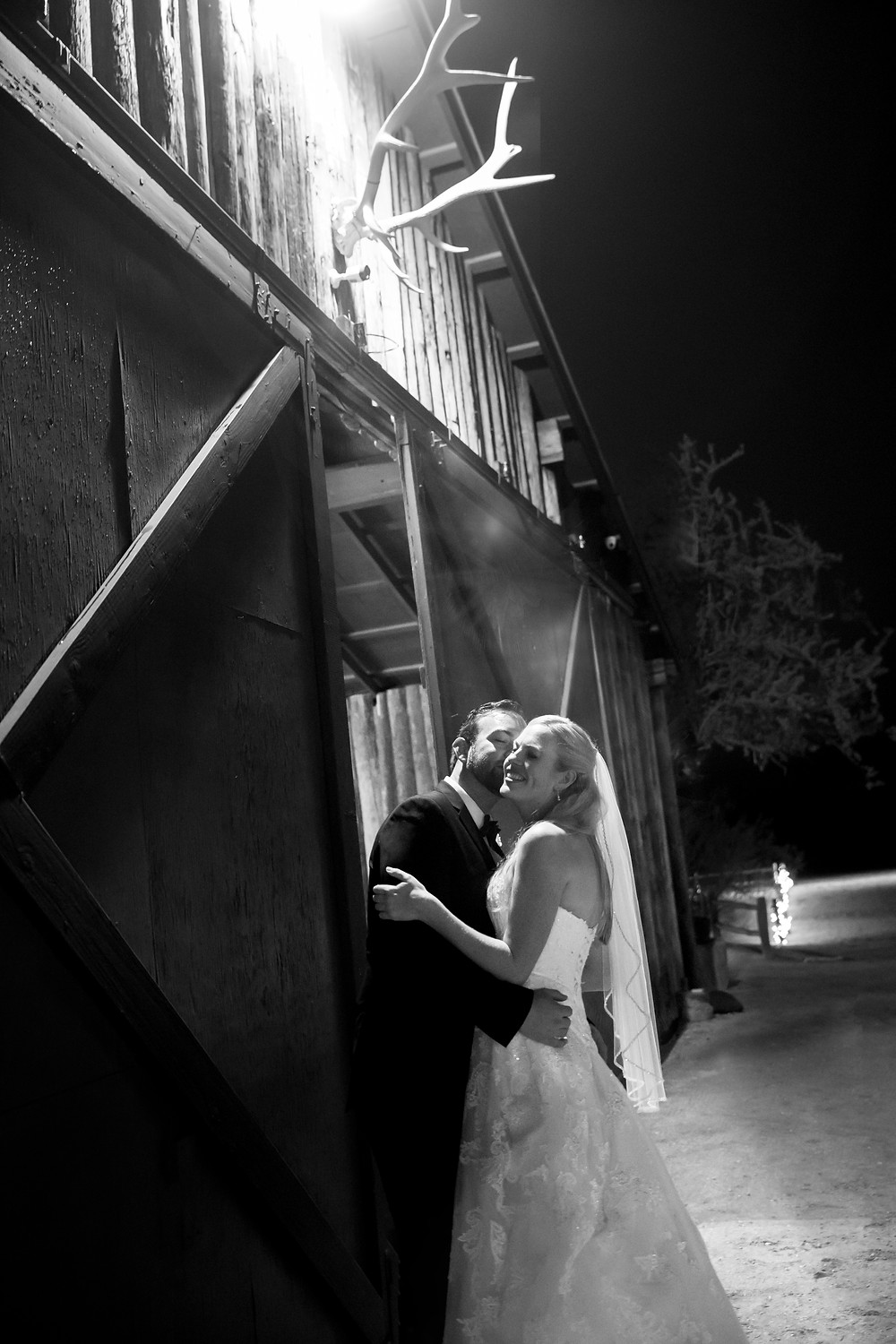 a newly wed couple kisses under a spotlight on their wedding day