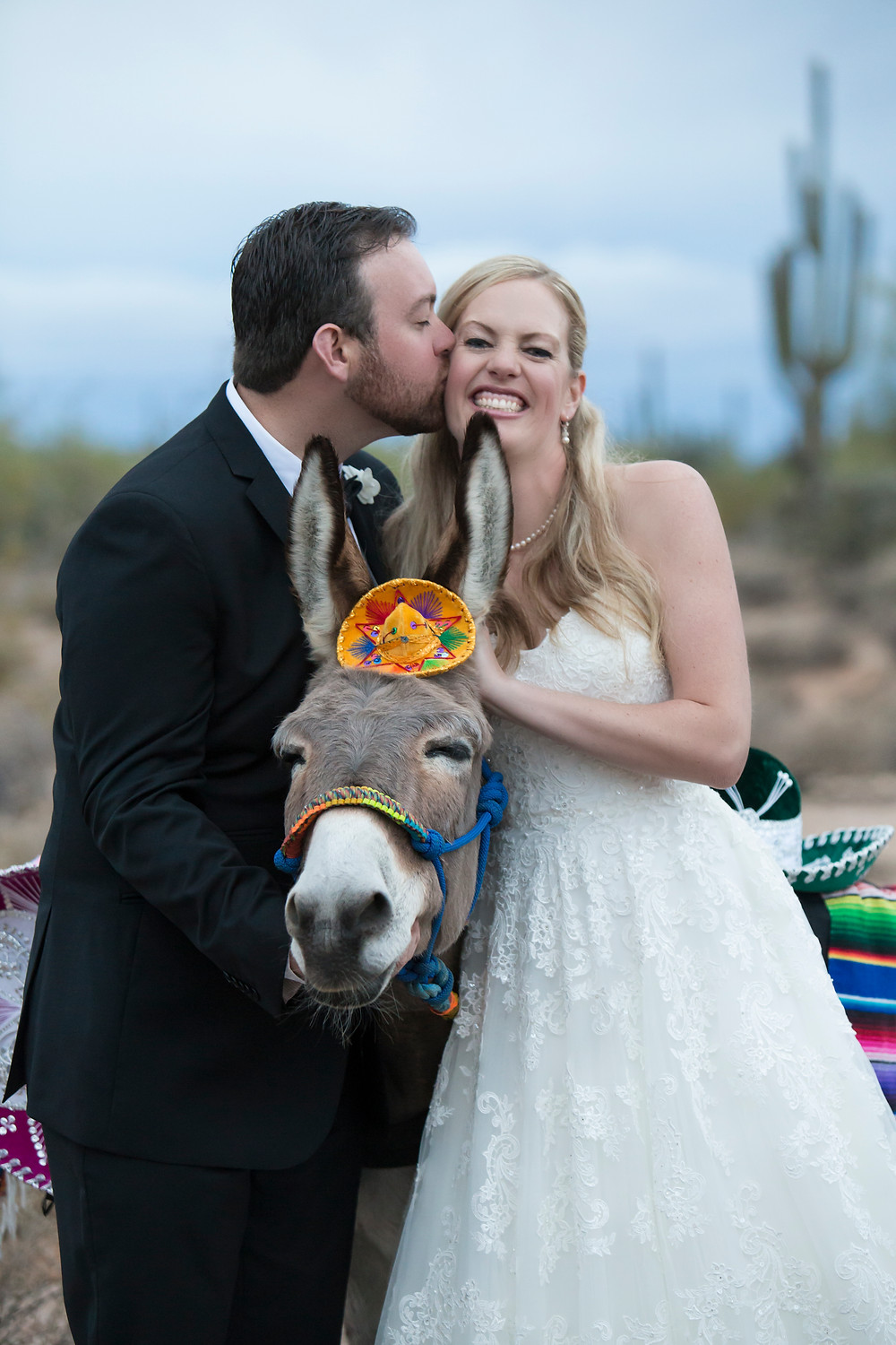 a groom kisses his bride over a beer burro