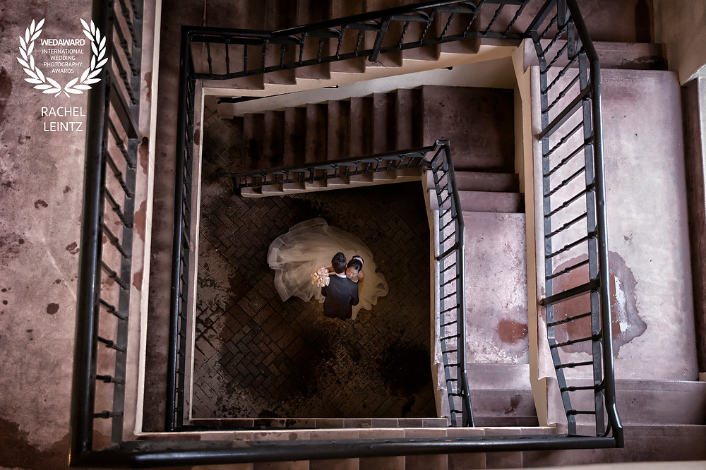 a bride and groom embrace in a rainy staircase