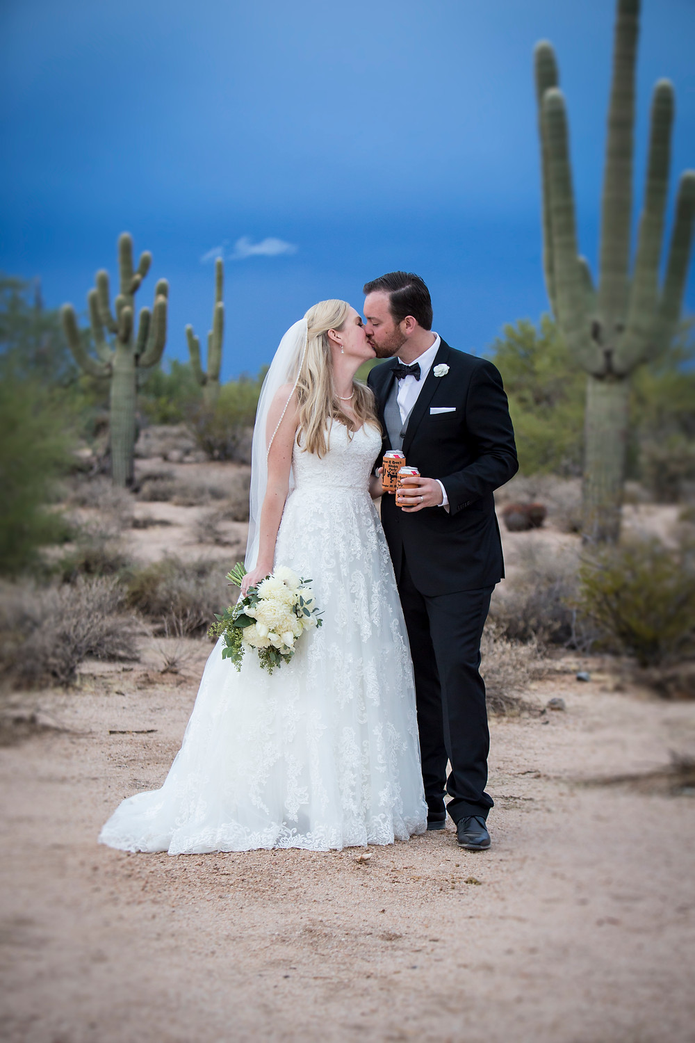 a bride and groom share a kiss in the desert