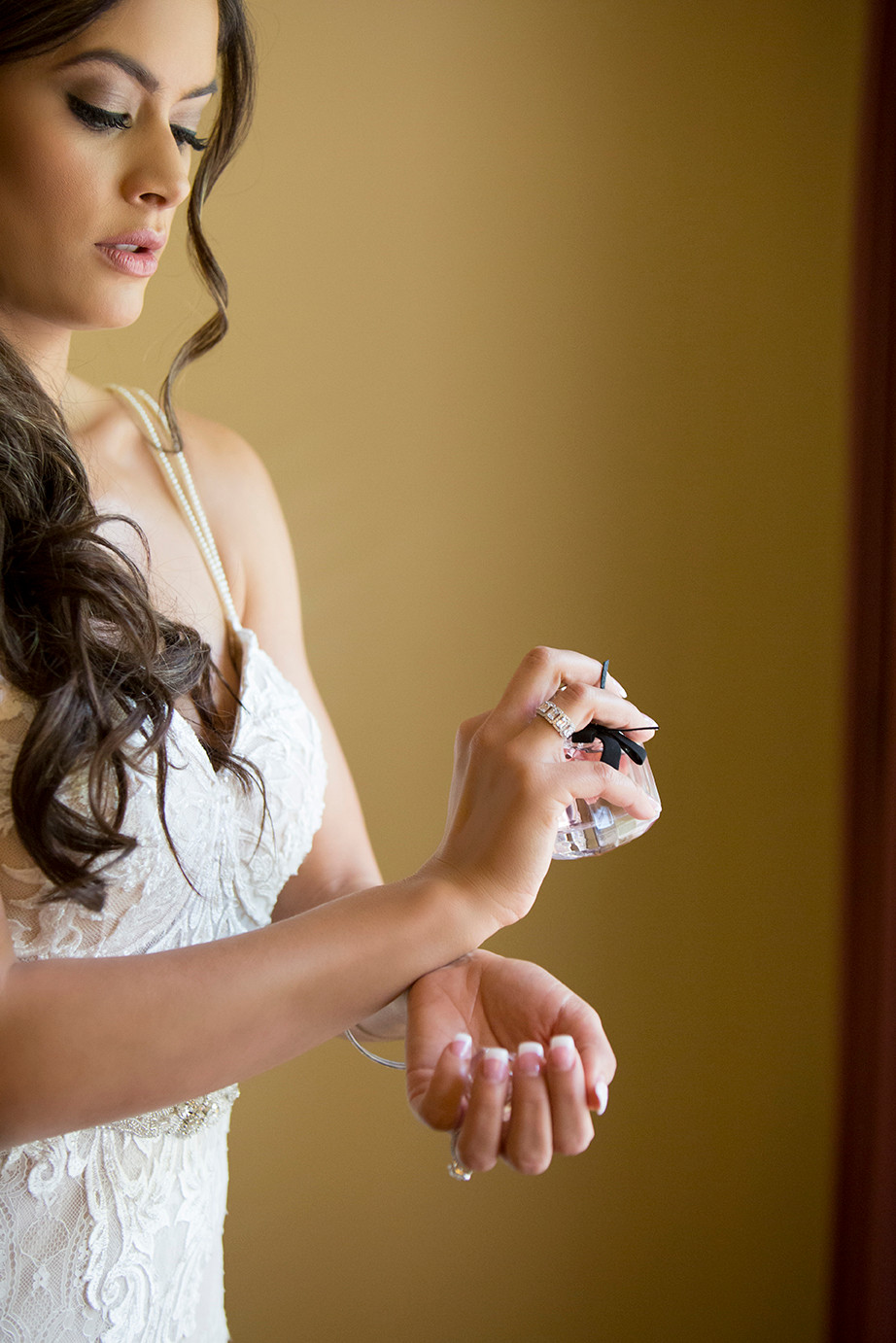 a bride putting on her perfume