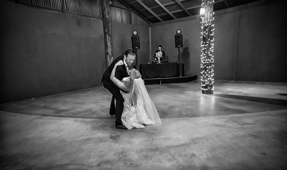 a groom dips his bride on the dance floor