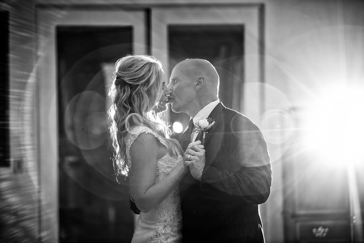 A couple kisses on the dance for during their first dance. Photograph by Rachel Leintz, Wedding Photographer