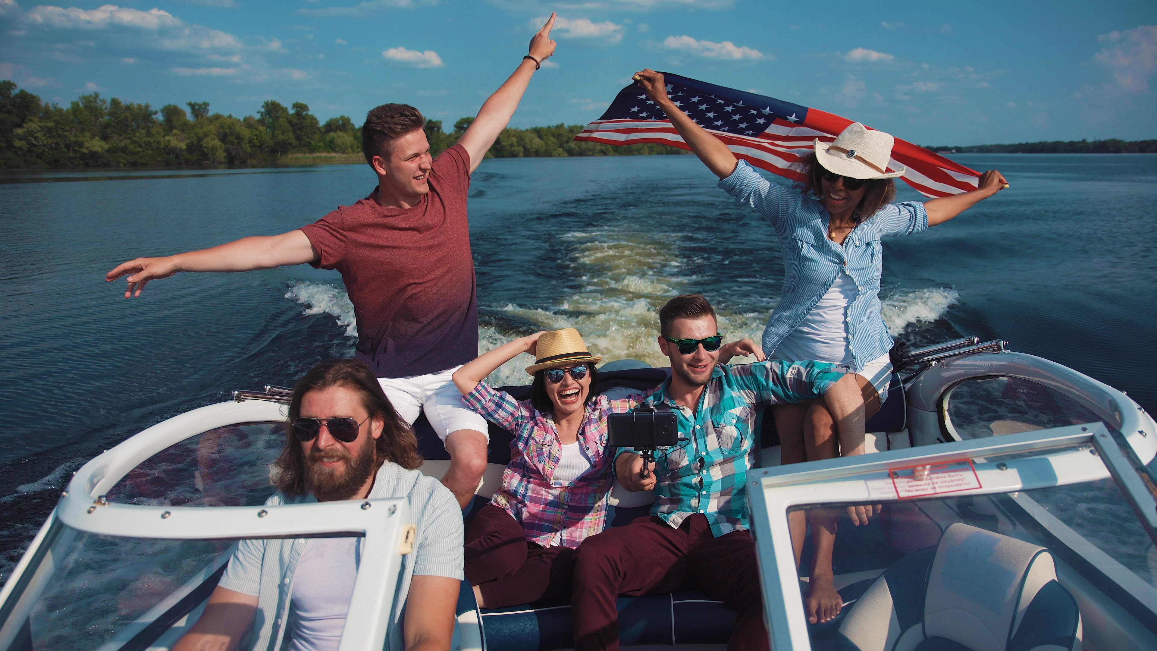 Group of cheerful friends on boat celebr