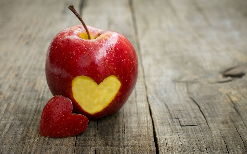stock photo of a red apple with a heart cut out on dark grain wood table