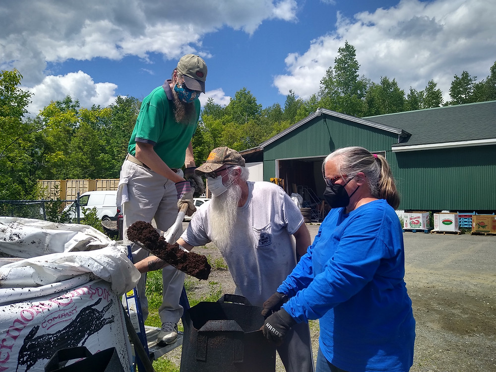 A photo of three people in action. Bob in a green shirt stands on a ladder lifting a shovel full of soil into a black cloth container held open by Marie in a blue shirt and her husband Chuck.