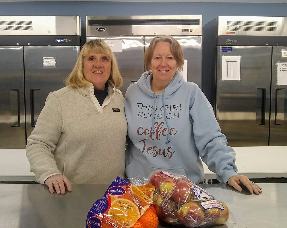 Left; Debbie L. and Right; Karen K. at the Dover Foxcroft Area Food Cupboard with a bag of apples and oranges in front of the stainless steel refrigerators.