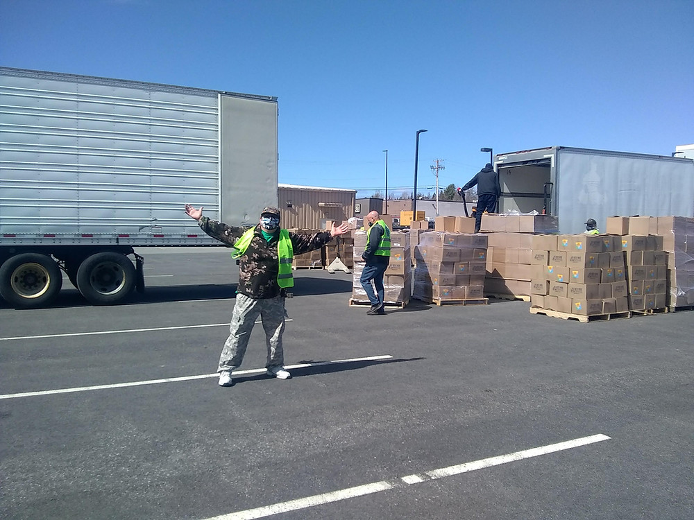 In the parking lot of Piscataquis County Ice Arena a volunteer wearing a lime green PRFC vest stands with arms wide open while volunteers in the background begin moving stacks of food boxes out from two large delivery trucks.