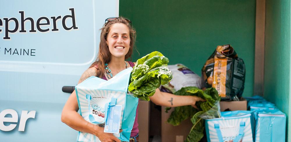 Merrilee Schoen stands in front of sliding doors on the Good Shepherd Van holding fresh produce.