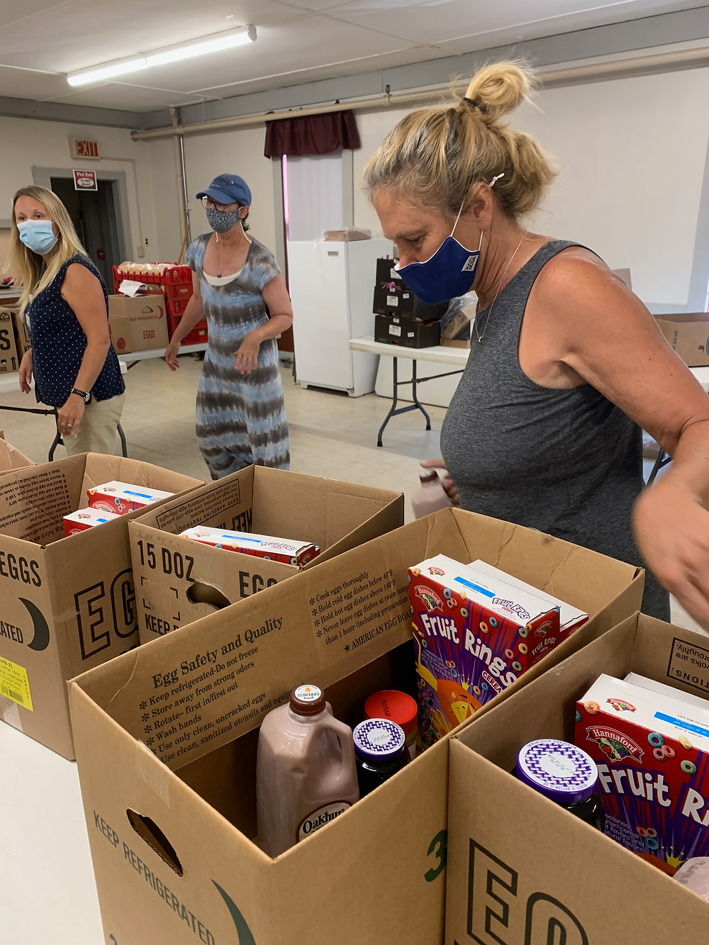 Dawn McGlaughlin, in a grey shirt, reviews contents of food boxes for the Free Summer Meal Program with additional volunteers to her side. Food items include milk, cereal, clementines, mac n cheese.
