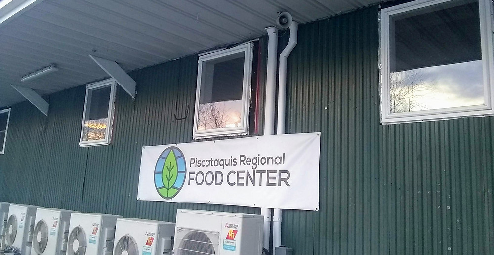 Photo of the side of the warehouse, green corregated metal walls. Sunset seen on the windows above heat pumps. Piscataquis Regional Food Center banner hung in center.