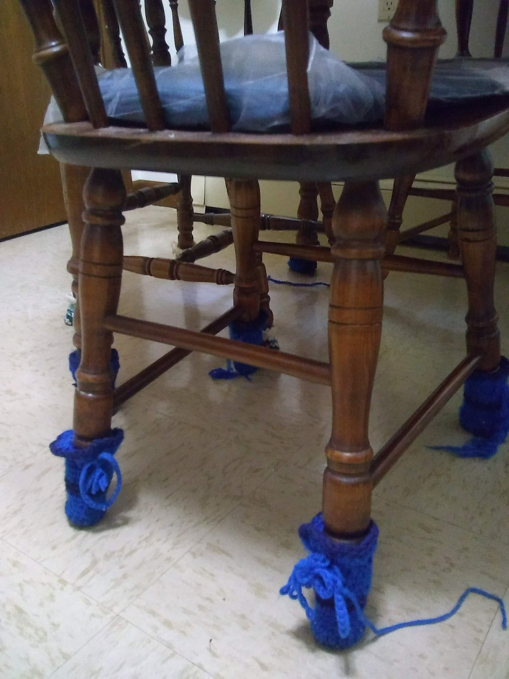 A photo of Theresa's hand-knit blue chair leg booties with light blue bows in her kitchen.