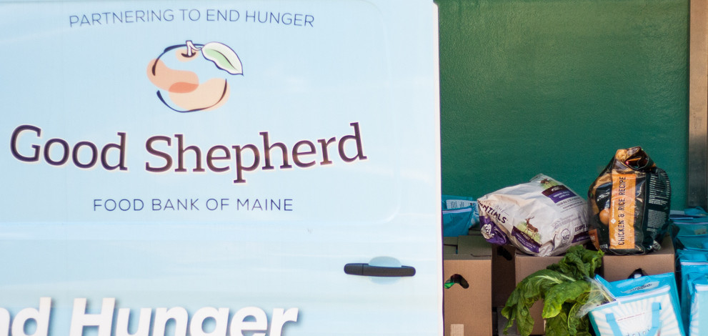 "Sliding door on Good Shepherd Food Bank Mobile Van showing fresh produce, commodities supplemental food boxes and dog food. The logo for Good Shepherd Food Bank of Maine is an apple and read ""Partnering to End Hunger""."