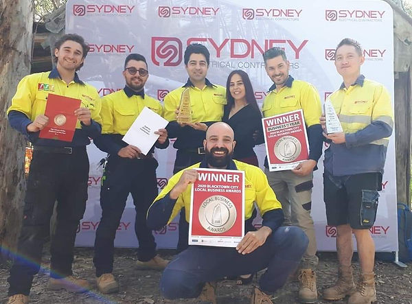 The Sydney Electrical Contractors team displaying the business of the year winner trophy and award.