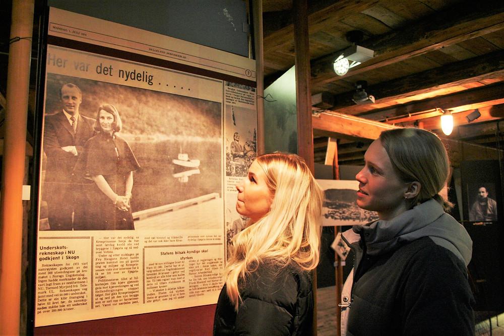 Silje Bergsnev (t.v) og Annika Honggard betrakter bildet av kronprinsparet da de besøkte Mosjøen og Sjøgata i 1974. Bildet er en forstørret kopi av Helgeland Arbeiderblad og er utstilt på Jacobsenbrygga, Helgeland Museum.