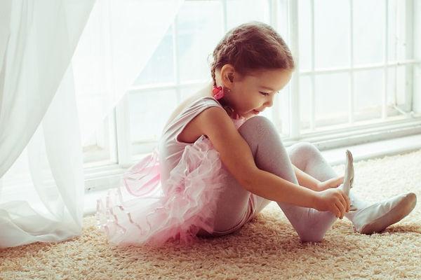 menina-sentada-no-chao-colocando-sapatos