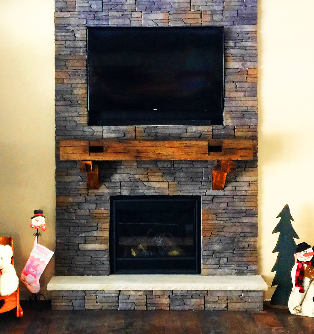 Stone veneer fireplace surround with a rustic wood mantle