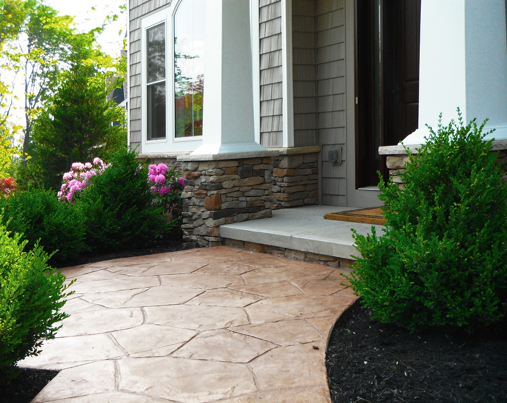 Stamped concrete walkway with stone veneer pillars on front porch
