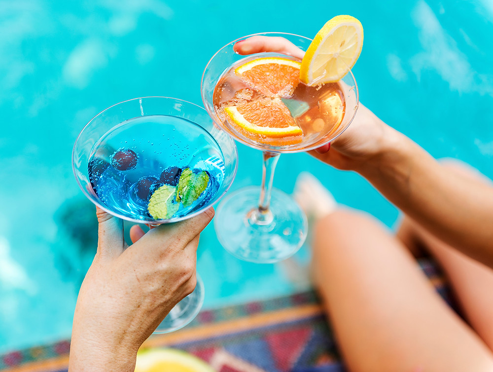 Two hands with cocktails by a pool for a pool deck masonry article