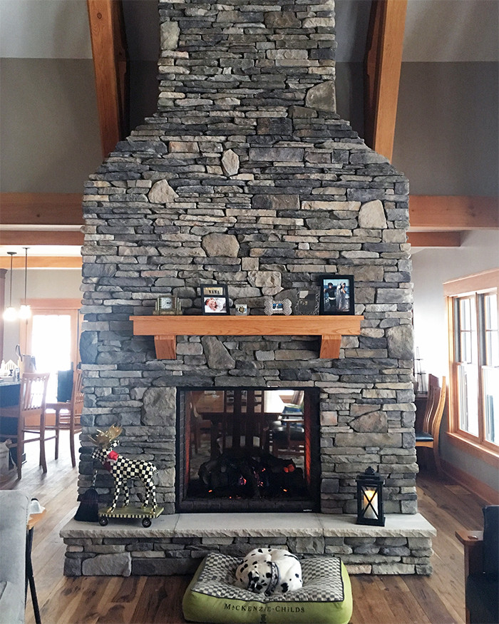 Stone veneer two-sided fireplace with wood mantle