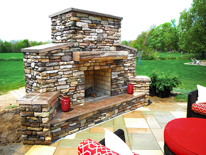 Stamped concrete patio with an outdoor stone fireplace