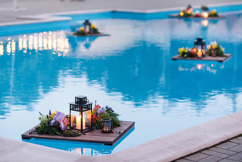 Pool deck with candles floating in the pool
