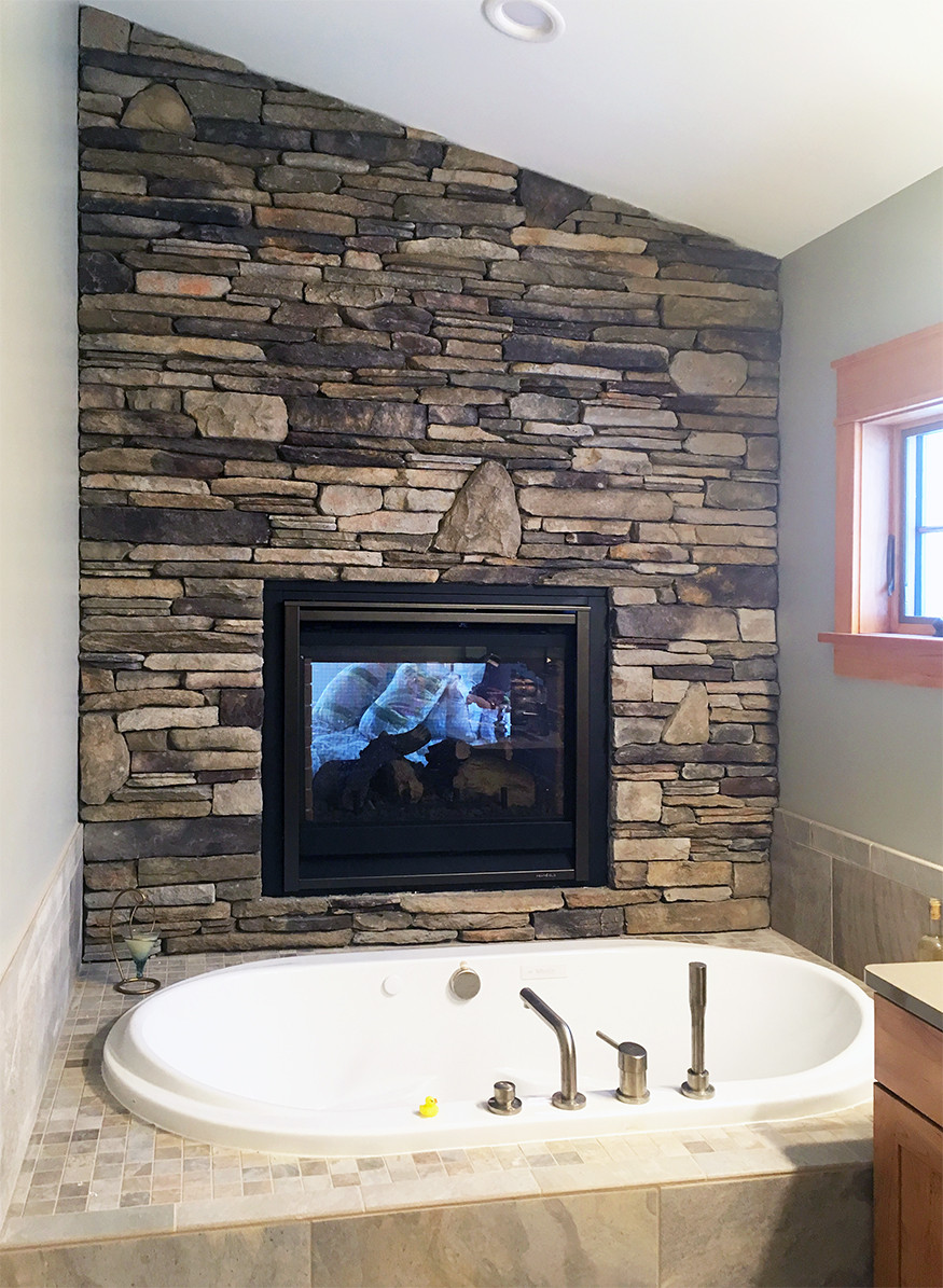 two-sided stone veneer fireplace with accent wall