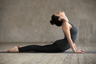 Young woman practicing yoga, doing Cobra