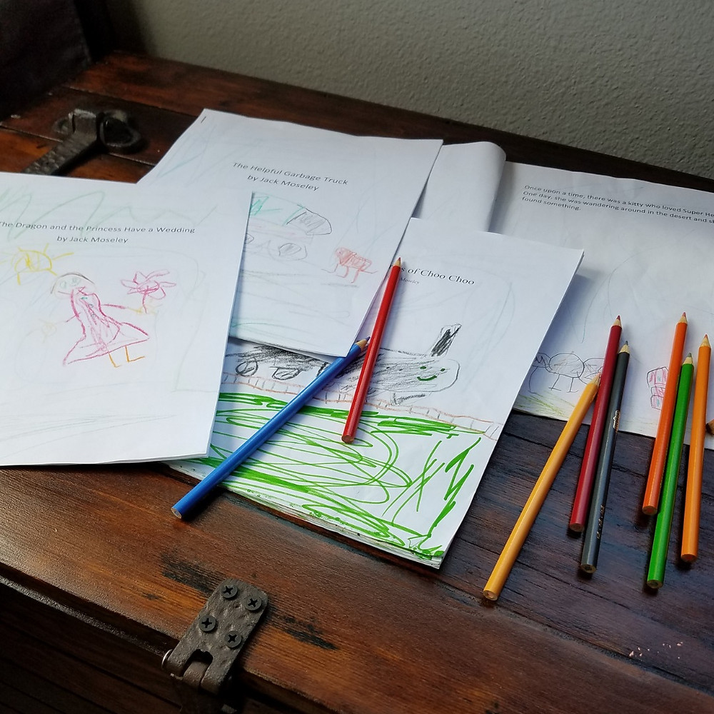 Several home-made books written and illustrated by a child along with many colored pencils on a rustic wooden table