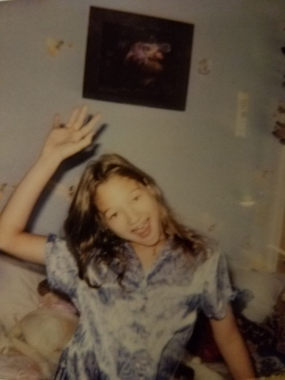 A young teenage girl with lavender pajamas in a room decorated with faries