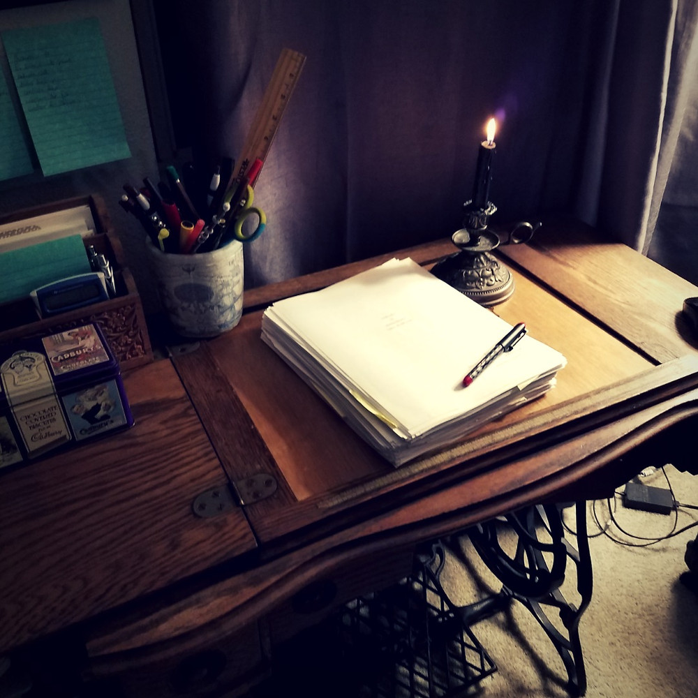 A writing desk converted from an old sewing table with a cast iron base. On the desk is a printed manuscript, lit candle in a candlestick, and jar of pens