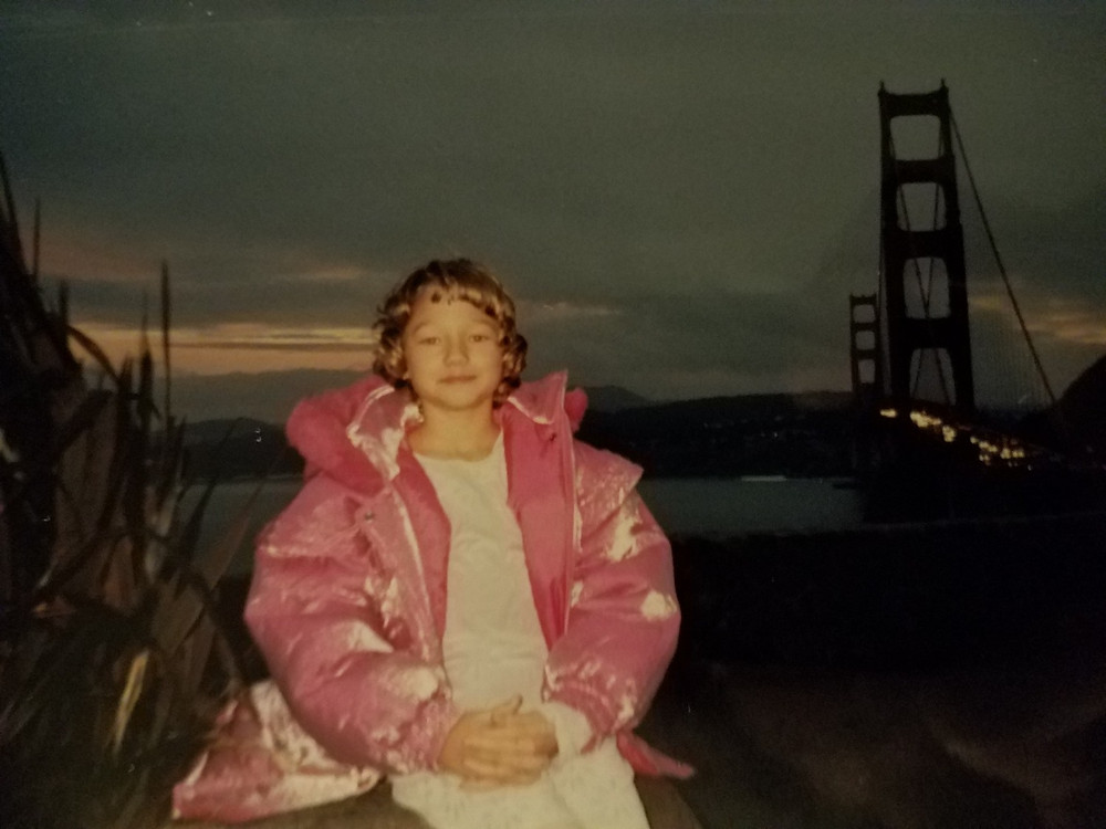A young girl with short, brown hair and a huge, pink coat in front of the Golden Gate Bridge.