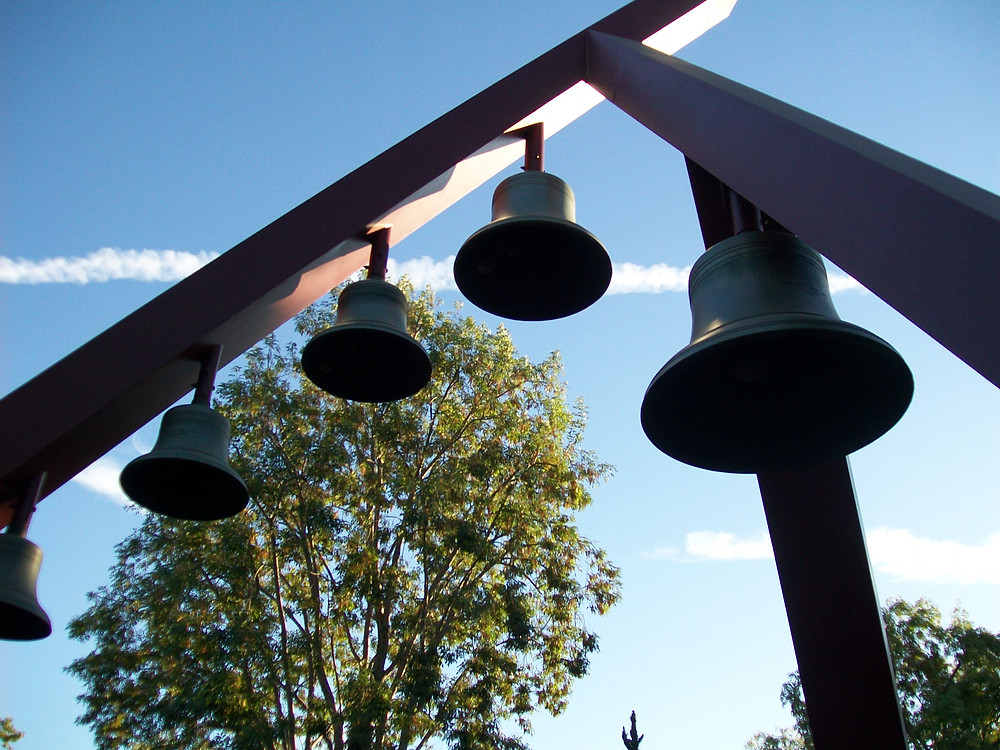 A modern structure made of three large, red supports and five old bells in front of a blue sky and several trees