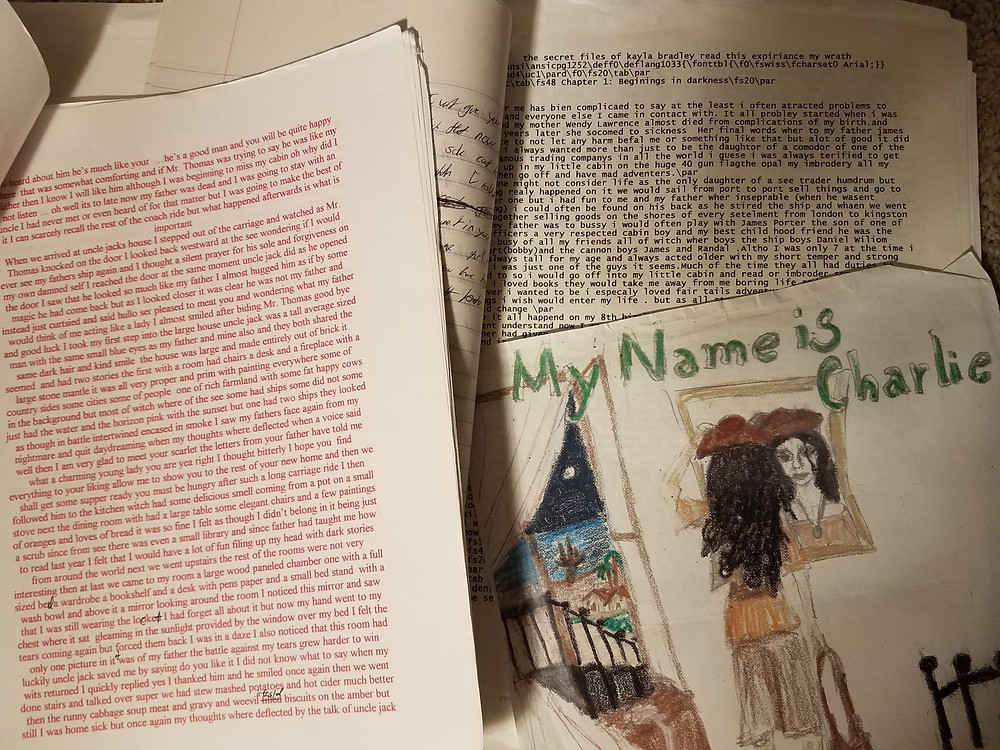 "Various pages of text and a child's hand-drawn book cover design reading ""My Name is Charlie"""