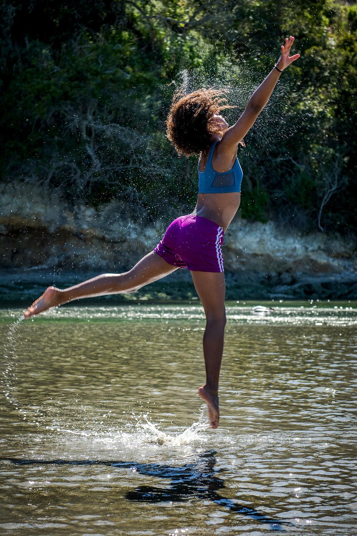 Mulher livre, dançando no leito de um riacho
