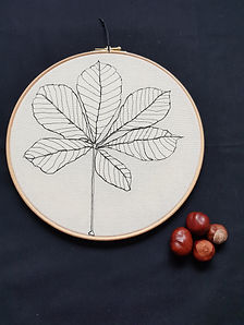 Gemma Rappensberger-an embroidered illustration of a autumnal leaf next to conkers.