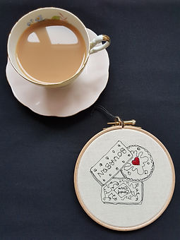 Gemma Rappensberger-an embroidered illustration of three biscuits next to a cup of tea.