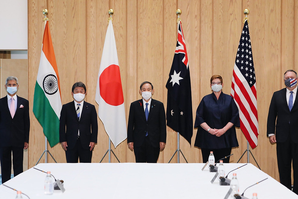 Representatives from India, Japan, Australia and the US wearing masks, standing between the Indian, Japanese, Australian and US flags
