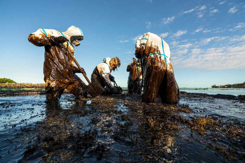 Four people in hazmat suits and gas masks cleaning oil spill from ocean