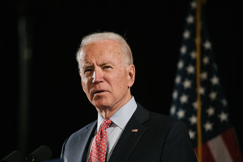Joe Biden standing in front of a black background with American flag