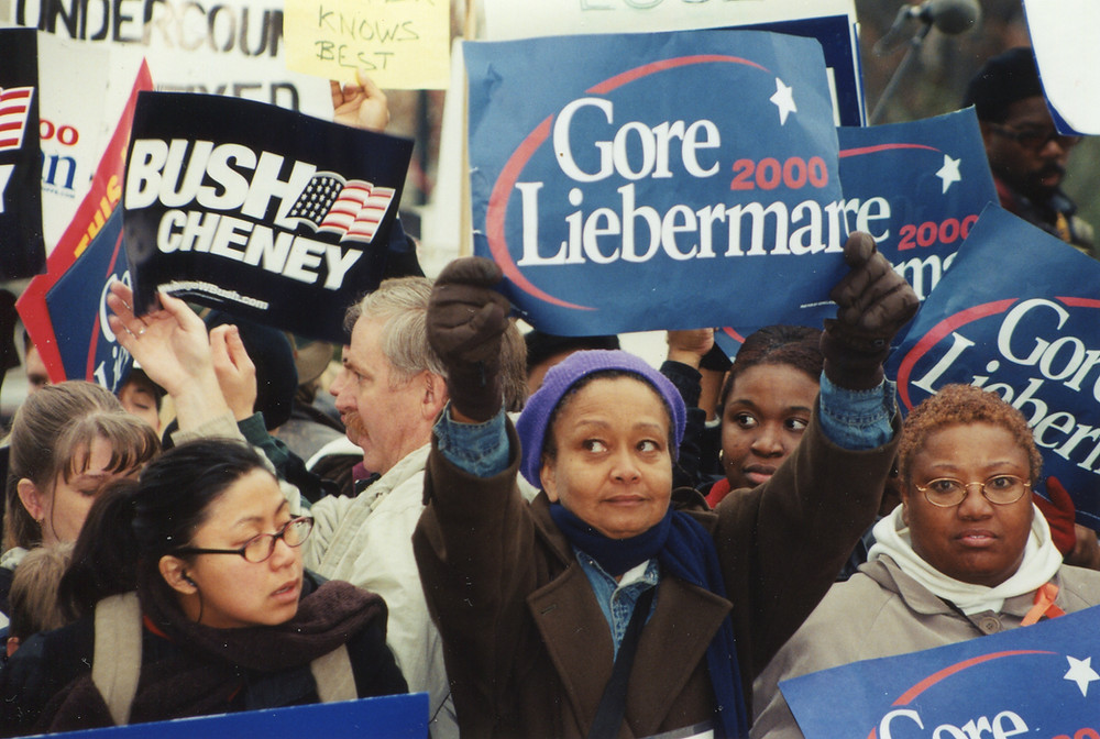 Crowd holding campaign posters that say 'Gore Lieberman 2000' and 'Bush Cheney'