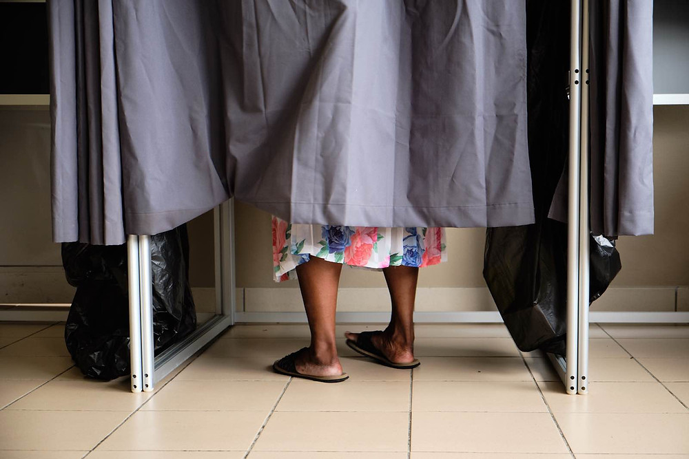 Voter's feet underneath a curtain of a voting booth