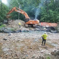 Contractor working to restore the stream and cleaning up sediment and damages.