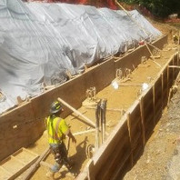 Contractor excavating Retaining Wall #3 bottom footing over caisson, as preparation before forming and placing re-bars.