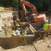 Contractor chipped concrete on caissons and excavating and placing #57 stone on subgrade for South Abutment footing.